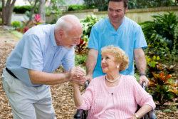 caregiver and elder couple at the garden