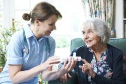 nurse advising senior woman on taking medication